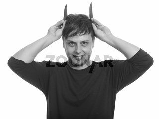 Studio shot of crazy man with peppers as horns smiling
