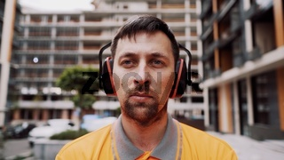Construction worker with ear muff working at construction site. Worker puts on ear defenders to protect against sound. Taking care of health, safety at work. Earplugs. Too loud sound, hearing damage