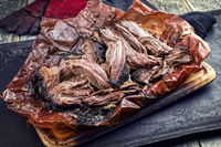 Traditional barbecue wagyu pulled beef in peach paper as closeup on a rustic board