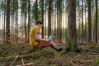 A man working outdoor with his laptop in a forest on the fresh air, home office in the green forest in front of your home.
