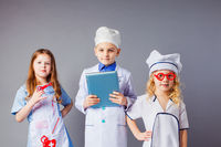Kids imagine future profession. Cute little doctors on grey background.
