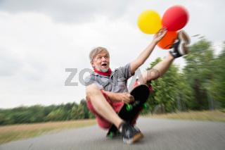 Alter Mann mit Luftballon auf Skateboard