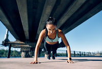 Young athletic woman doing push ups outdoors in urban city background