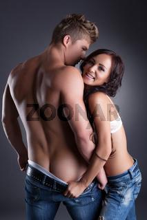 Shot of playful woman bares her boyfriend's ass