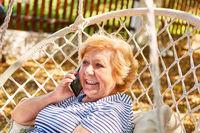 Glückliche Senior Frau telefoniert mit Smartphone