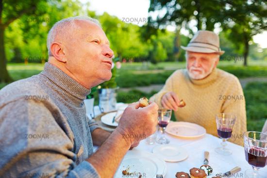 Mann isst Kuchen im Garten mit Freunden