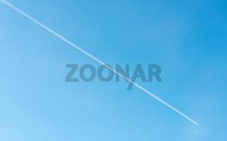 Jet plane flying and its contrail on blue sky