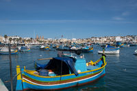 Maltese fishing village of Marsaxlokk with traditional painted boat in Foreground