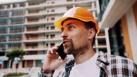 Caucasian male construction worker in orange hard hat and plaid shirt talking on phone at construction site. Architecture theme. Male profession. Foreman controls construction process by smartphone