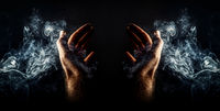 hand in smoke ona black background, praying hands.