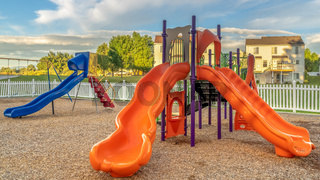 Pano frame Bright orange and blue slides at a colorful fun playground for children