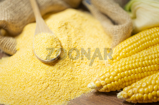 Ripe young sweet corn cob spoon and cornmeal close up