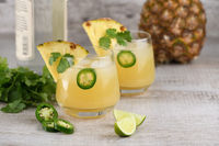 Tequila cocktail with pineapple juice, jalapeno  slices and cilantro, cooled with ice