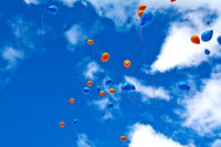 Balloons orange and blue in sky