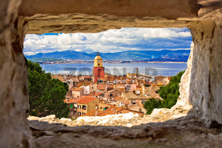 Saint Tropez village church tower and old rooftops view through stone window