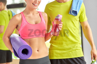couple with water bottles , mat and towel in gym