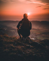 Hiker with backpack sitting on mountain and enjoying sunset