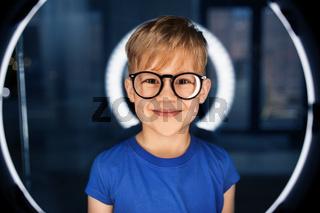 boy in glasses over illumination in dark room