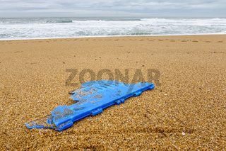 Piece of blue plastic on beach, pollution concept