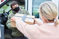 Paketbote mit Mundschutz nimmt Paket Lieferung an