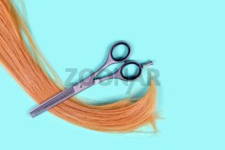 Blonde Haarsträhne und Effelierschere auf blauem Grund