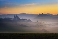 Spis Zipser Castle above valley at sunrise in fog