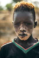 MUNDARI TRIBE, SOUTH SUDAN - MARCH 11, 2020: Teen boy with ritual dirt on face and in t shirt looking at camera while living in Mundari Tribe village on sunny day in South Sudan, Africa