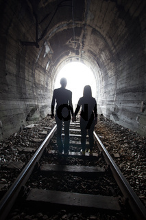 Couple walking together through a railway tunnel