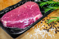 Beef steak in vacuum skin packaging and spices on wooden chopping board