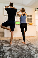 White caucasian couple do tree pose yoga at home