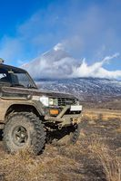 Modified Japanese car SUV Toyota Land Cruiser Prado on mountain background eruption active volcano