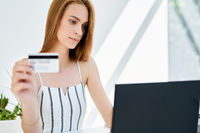 Young woman shopping online with laptop and credit card