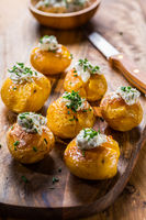 Small oven baked potatoes with sour cream with butter and chives