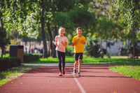 Kids run. Healthy sport. Child sport, heterosexual twins running on track, fitness. Joint training. Running training outdoor brother and sister pre-teen. Jogging with friend. Children athletes