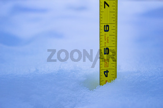 Measuring the snow depth with yellow ruler 4 feet