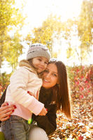 Happy mother and daughter in autumn park