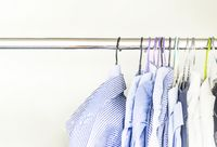 A group of men's shirts of various colors hung with hangers inside a wardrobe