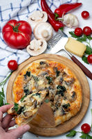 Slice of pizza with mushrooms, spinach and cheese.