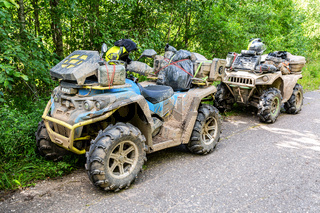 Off-roader quad bikes after driving on extremely dirty rural road