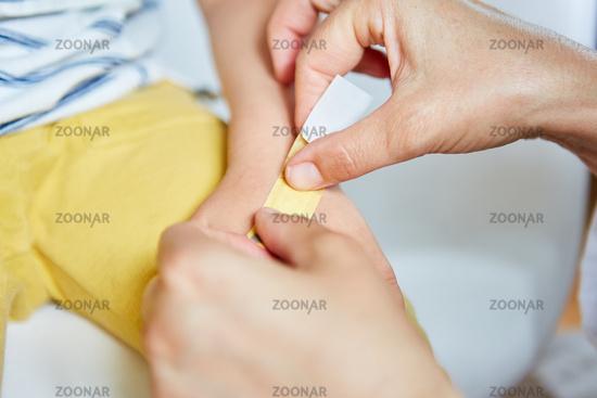 Kinderarzt klebt Pflaster auf die  Hand von Kind