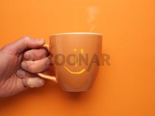 Orange coffee mug with a smiling icon