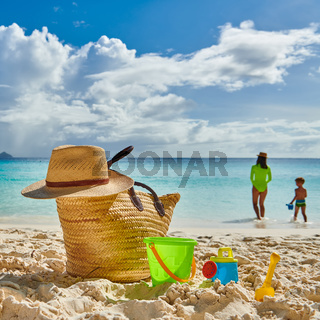 Toddler boy on beach with mother. Beach bag and toys.