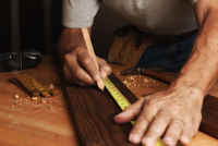 Closeup of a man in his workshop marking a board for cutting.