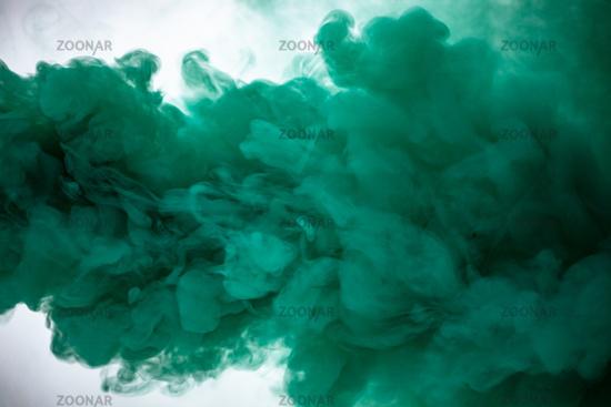 Green smoke bomb exploding against white background