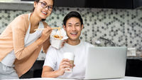 Asian couple working from home with take out food.
