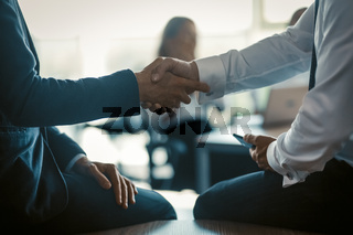 Handshaking of two business colleagues on modern office background. Business concept. Close up shot