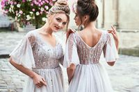 Two beautiful bridesmaids ladies in gorgeous elegant stylish light grey silver floor length open back dresses in old beautiful European city on a wedding day.