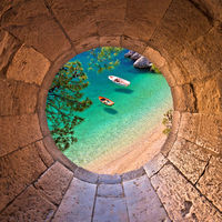Hiden beach in Brela with boats on emerald sea aerial view through stone window