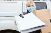 Paketbotin trägt Mundschutz und bittet um Unterschrift