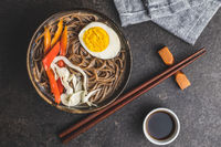 Asian noodle soup with soba noodles, vegetable and egg in bowl.